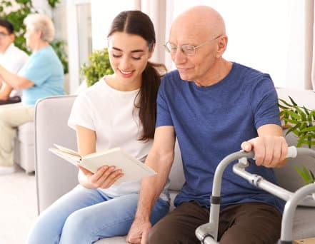 caregiver and patient reading a book