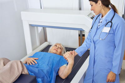 senior women holding hand of doctor in radiology while getting bone density measurement