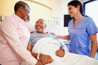 nurse talking to senior couple holding hands in hospital room smiling