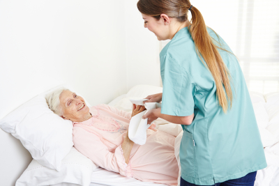 geriatric nurse washing bedridden senior woman and drying her hands in nursing home